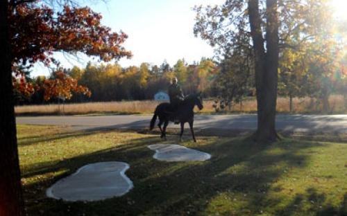 Horseback riding past Bunyan footprints at Barclay Town Hall & Rest area