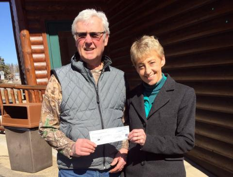 Jim Fogarty CEO of Pelican Lakes Conservation Club shown here handing $500 donation toward the Linda Ulland Memorial Gardens Talking Boxes project to Lynn Scharenbroich of (PBSBA).