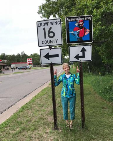 Scenic Byway board member, Lynn Scharenbroich stands beside new route signage installed this spring along the Scenic Byway county roads.